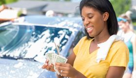 Confident African American teenage girl counts money at car wash