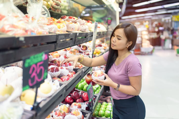 Beautiful Asian women shopping vegetables and fruits in supermarket.